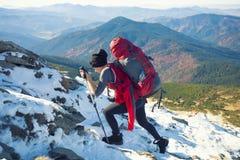 Alpinista che scala un pendio nevoso Immagini Stock