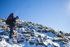 Alpinista che scala un pendio nevoso Fotografie Stock