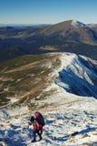 Alpinista che scala un pendio nevoso Fotografie Stock Libere da Diritti