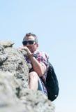 Alpinista che scala una scogliera sopra la montagna Fotografia Stock