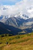 Alpinista che segue l'itinerario famoso di trekking in montagne di Caucaso Immagini Stock