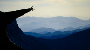 Alpinista che si siede sul outcropping roccioso Immagine Stock