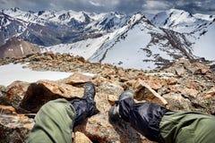 Alpinista che si siede sulla montagna Fotografia Stock