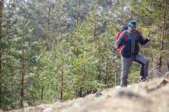 Alpinista con alpinismo dei pali sulla montagna Fotografia Stock