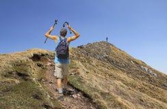 Alpinista con i bastoni da passeggio, facenti un'escursione verso la sommità della montagna Immagini Stock Libere da Diritti