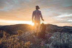 Alpinista con il suo cane nelle montagne Fotografie Stock Libere da Diritti