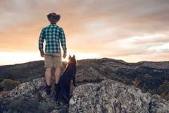 Alpinista con il suo cane nelle montagne Fotografie Stock