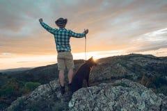 Alpinista con il suo cane nelle montagne Immagine Stock