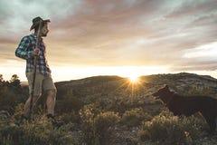Alpinista con il suo cane nelle montagne Fotografia Stock