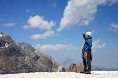 Alpinista con strumentazione rampicante sulla parte superiore del Fotografia Stock