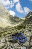 Alpinista dell'attrezzatura nella valle dopo la finitura della salita Fotografia Stock