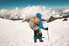 Alpinista dell'uomo che scala con lo zaino in montagne Fotografia Stock