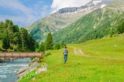 Alpinista della giovane donna che cammina tramite la torrente montano Fotografia Stock