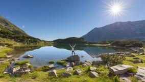 Alpinista della ragazza di solitudine su roccia vicino al lago Fotografia Stock