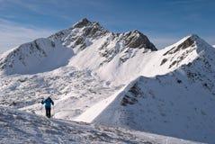 Alpinista dello sci con il picco di montagna rocciosa nevoso nei precedenti Fotografie Stock Libere da Diritti