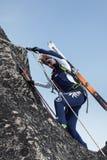 Alpinista dello sci della donna che scala sulla roccia su una corda Immagine Stock Libera da Diritti