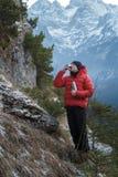 Alpinista di rilassamento che beve bevanda calda dalla boccetta di vuoto d'acciaio al fondo nevoso delle montagne di inverno Fotografia Stock Libera da Diritti