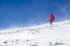 Alpinista dziewczyna wycieczkuje w snowed mountaind z ciężkim wiatrem fotografia royalty free