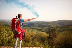 Alpinista femminile che invia il segnale di fumo al gruppo delle viandanti fotografia stock