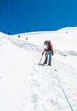 Alpinista femminile che sale un ghiacciaio Fotografie Stock