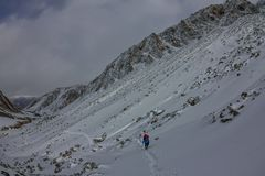 Alpinista femminile con lo zaino, il casco ed il cablaggio con la scalata in montagna Fotografie Stock Libere da Diritti