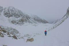 Alpinista femminile con lo zaino, il casco ed il cablaggio con la scalata in montagna Immagini Stock