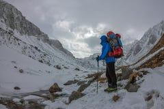 Alpinista femminile con lo zaino, il casco ed il cablaggio con la scalata in montagna Immagine Stock