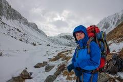 Alpinista femminile con lo zaino, il casco ed il cablaggio con la scalata in montagna Fotografie Stock