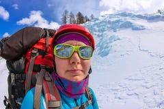 Alpinista femminile del ritratto con lo zaino, il casco ed il cablaggio con la scalata in montagna Fotografie Stock