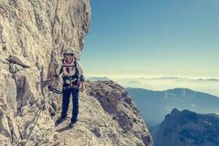 Alpinista femminile felice che scala via il ferrata Fotografia Stock