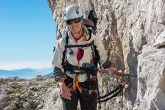 Alpinista femminile felice che scala via il ferrata Fotografie Stock