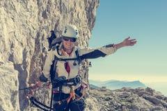 Alpinista femminile felice che scala via il ferrata Fotografia Stock Libera da Diritti