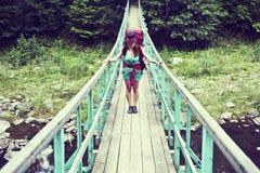 Alpinista femminile felice che sta su un ponte di legno sopra una torrente montano che trabocca con l'eccitazione con la gloria e Fotografia Stock