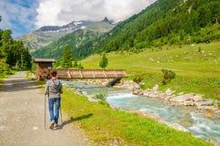 Alpinista femminile tramite la torrente montano in alpi Immagine Stock