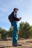 Alpinista fra l'escursione dei pini Fotografie Stock Libere da Diritti