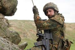 Alpinista militare munito che appende sulla corda Fotografie Stock