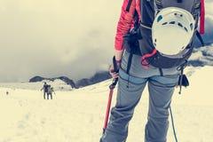 Alpinista que mira abajo de la cuesta Imagenes de archivo