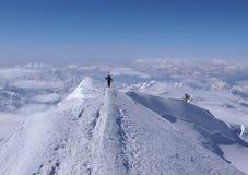 Alpinista remoto maschio dello sci che fa un'escursione lungo uno stretto e una cresta esposta della sommità di alto picco alpino Fotografie Stock Libere da Diritti