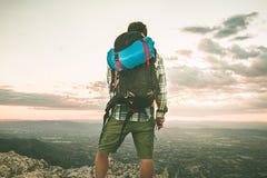 Alpinista sopra una montagna con uno zaino foto Fotografia Stock
