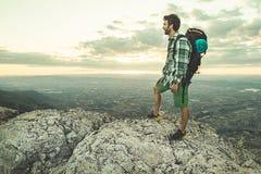 Alpinista sopra una montagna con uno zaino foto Immagine Stock