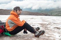 Alpinista stanco che si siede sullo zaino Fotografie Stock Libere da Diritti