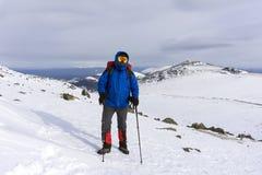 Alpinista su un fondo di un paesaggio della montagna di inverno Immagini Stock Libere da Diritti