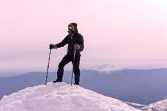 Alpinista su una cima nevosa della montagna Fotografia Stock
