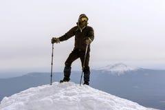 Alpinista su una cima nevosa della montagna Immagine Stock