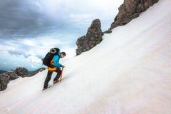 Alpinista in un pendio nevicato ripido Immagine Stock
