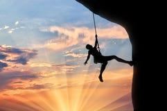 Alpinista wspina się faleza zmierzch Zdjęcia Royalty Free
