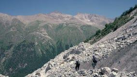 Alpinistas que caminan en la montaña de la nieve Grupo turístico que sube un pico de montaña de la nieve almacen de video