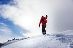 Alpiniste atteignant le sommet d'une crête neigeuse dans la saison d'hiver photo stock