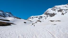 Alpiniste augmentant le ski voyageant sur la pente neigeuse vers le sommet de montagne Concept de conquérir des adversités et d'a Photographie stock