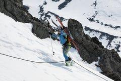 Alpiniste de ski de jeune femme s'élevant sur la corde sur des roches Image libre de droits